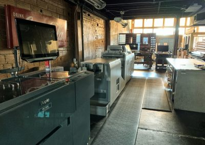 Xpresso Print Cafe wall of printers and print gear